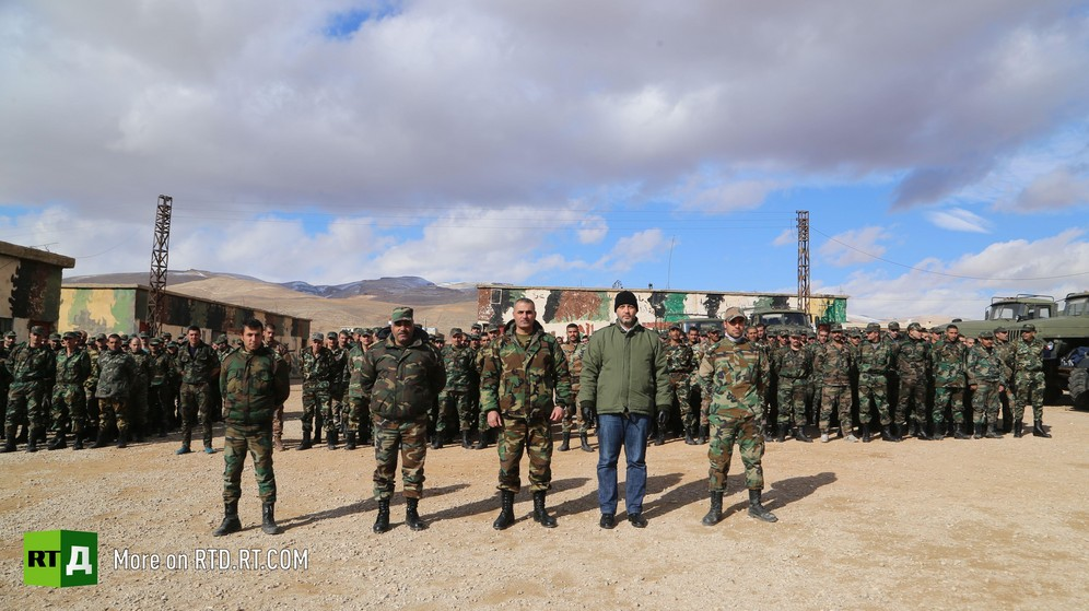 A Syrian army unit made up of amnestied fighters is standing in uniform in front of barracks. Five officers stand to attention in the foreground, under a bright blue sky with large clouds. Taken while filming RTD documentary about Syrian amnestied fighters Amnesty in Wartime.