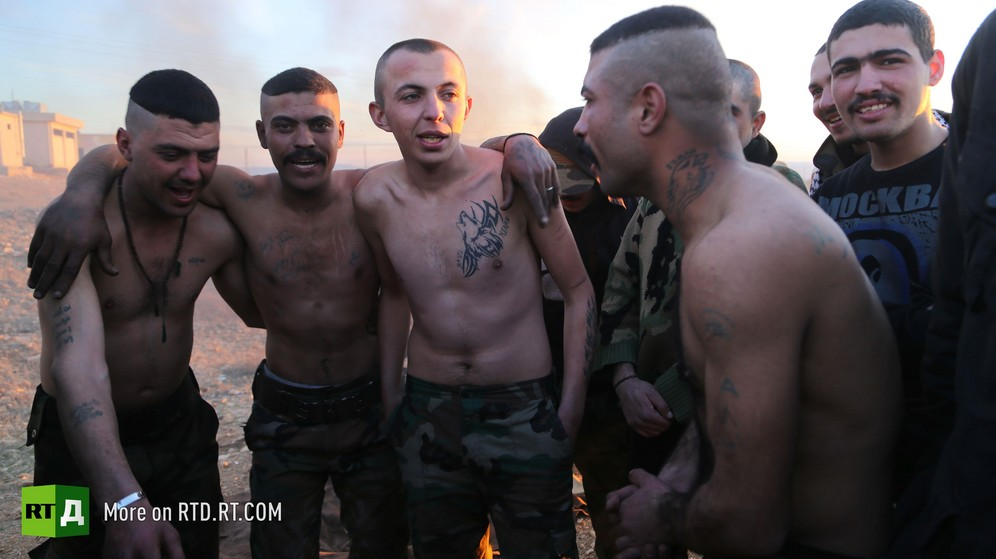 Bare-chested tatooted young Syrian male conscripts hug each other during Army training camp. Taken while filming RTD documentary about Syrian amnestied fighters Amnesty in Wartime.