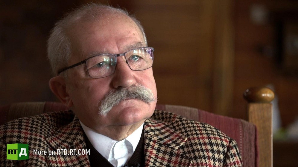 Headshot of elderly Polish farmer with a grey moustache wearing a tweed jacket. Still taken from RTD documentary Apples of Discord.