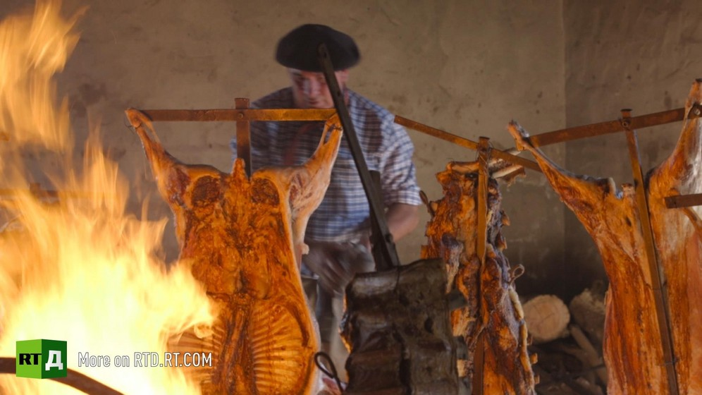 Beef carcasses hung on stakes are being roasted over an open fire, with a man earing a beret in the background. Still taken from RTD documentary Argentinian DNA: A Different Argentina.