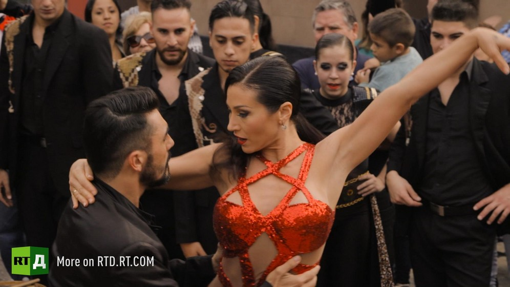 Man wearing a black shirt and woman in red dress dancing surrounded by a crowd in rural Argentina. Still taken from RTD documentary Argentinian DNA: A Different Argentina.