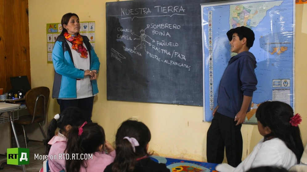 a young boy wearing a traditional beret stands in front of the chalk board and a map of Argentina, to answer his teacher, standing to the left of the classroom, in a rural Argentina school. Still taken from RTD documentary Argentinian DNA: A Different Argentina.