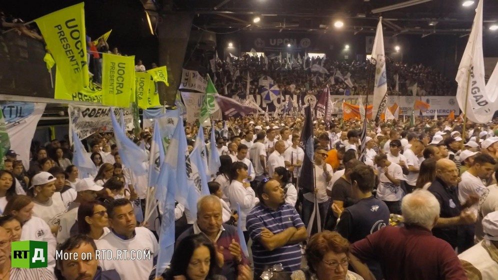 Crowd waving flags in a hall at a political rally. Still taken from RTD documentary Argentinian DNA: The Fracture.