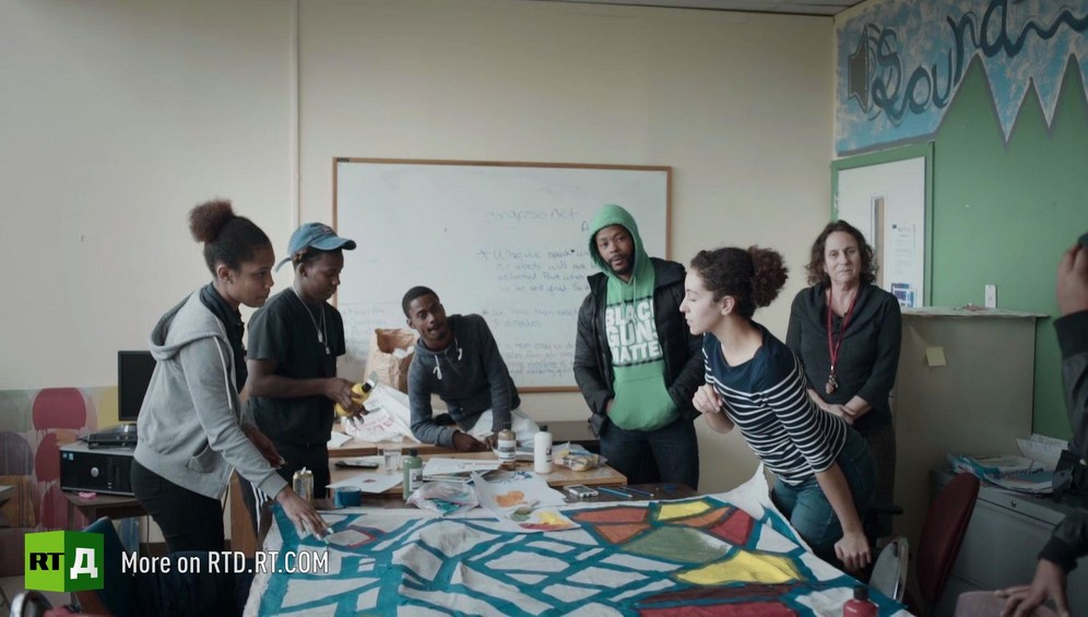 African American students stand around the large sheet of paper they are painting during art class at YESPHilly second chance high school in Philadelphia, USA, while being wacthed by school founder Taylor Frome and Black Guns Matter activist Maj Toure. Still taken from RTD documentary Black Lives 5. Agents of Change