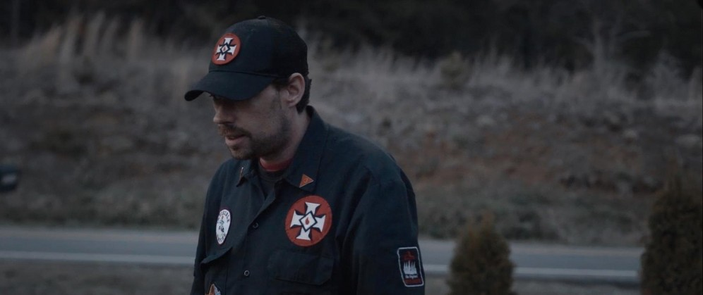 A man with a moustache is wearing a KKK uniform with a baseball cap and blue shirt with KKK badges sewn on. Still taken from RTD documentary Black Lives 8: Deadlock.