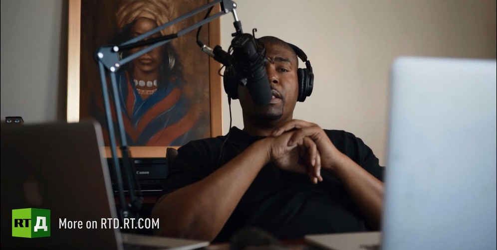 Tariq Nasheed is wearing headphones and speaking into a microphone. Still taken from RTD documentary Black Lives 8: Deadlock.