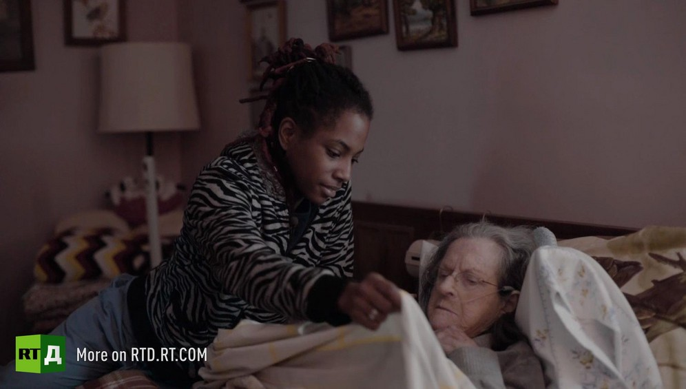 Young African American woman holding up sheets to tuck in an elderly White woman in bed. Still taken from RTD Documentary film Black Lives 6. Illusion about single-parent families and teenage parenthood in Black America.