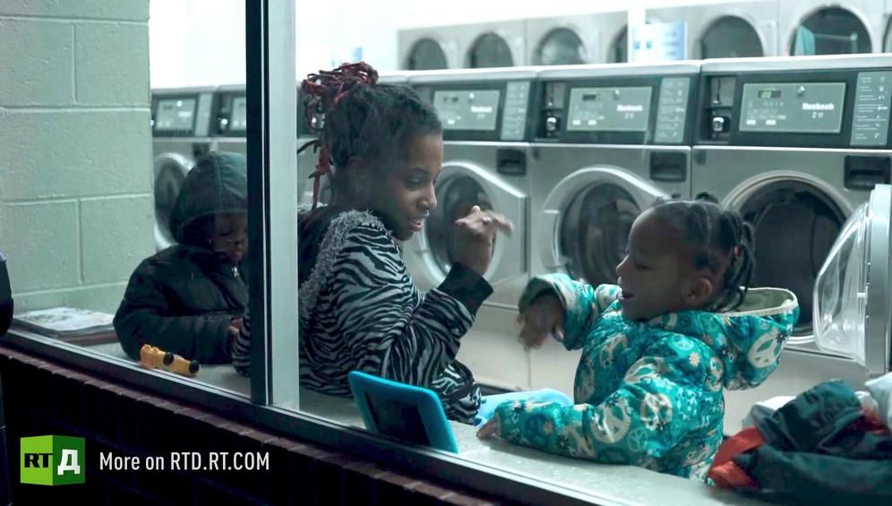 African American mother interacting with her daughter, who is playing on a tablet, while her son sits next to her in a laundromat. Still taken from RTD Documentary film Black Lives 6. Illusion about single-parent families and teenage parenthood in Black America.