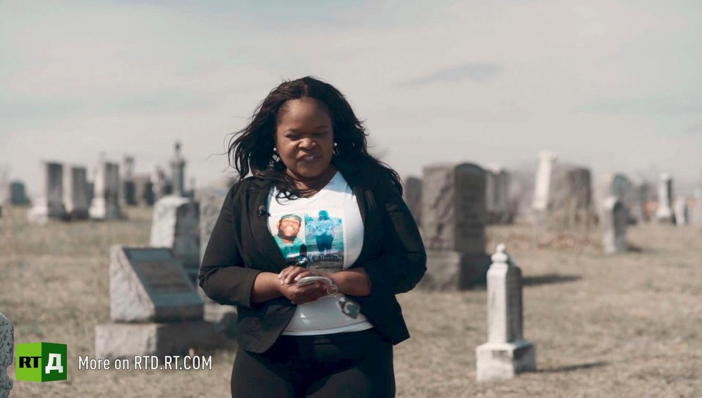 African American woman wearing a t-shirt with pictures of sons who were shot, standing in front of headstones in a cemetery in the sun. Still taken from RTD Documentary film Black Lives 6. Illusion about single-parent families and teenage parenthood in Black America.