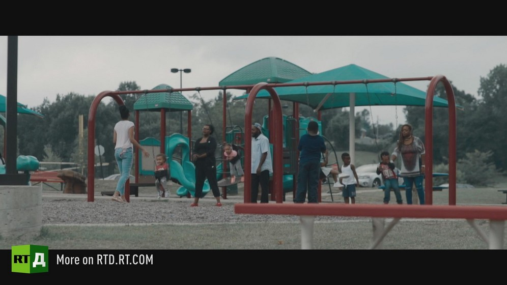 Playground with African American families playing on swings. Still taken from RTD documentary, Black Lives 10: Trap.