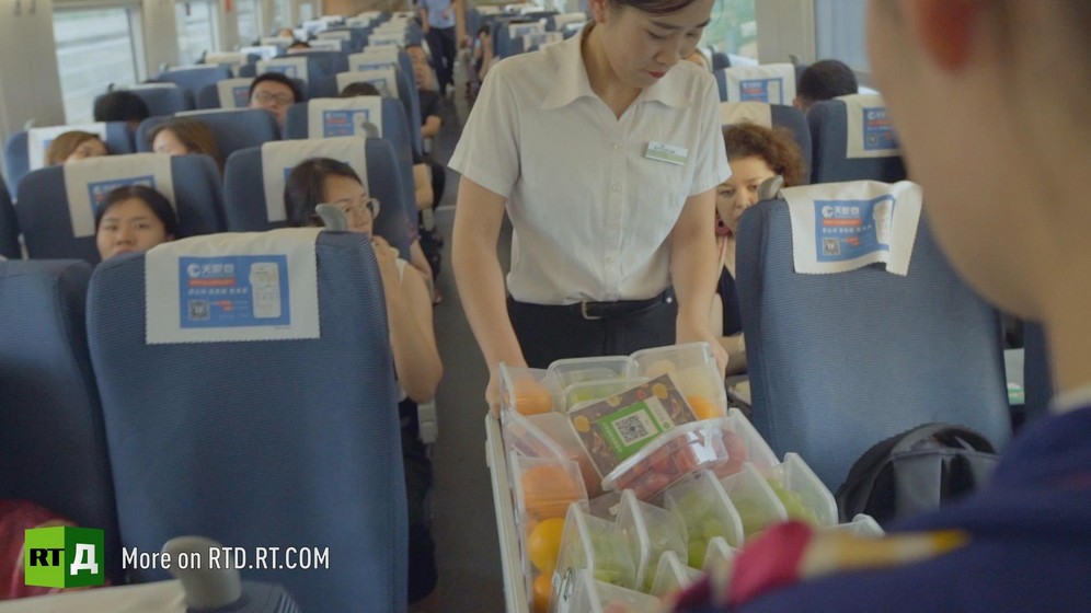 In a Chinese high speed train, a female attendant guides a trolley with food.  Still taken from RTD documentary Chinese Speed  in the This is China series.