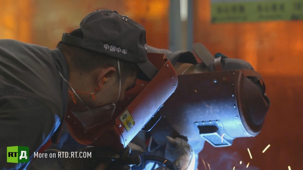 At a Chinese high speed train manufacturing plant, two welders wearing protective helmets are producing sparks.  Still taken from RTD documentary Chinese Speed  in the This is China series.
