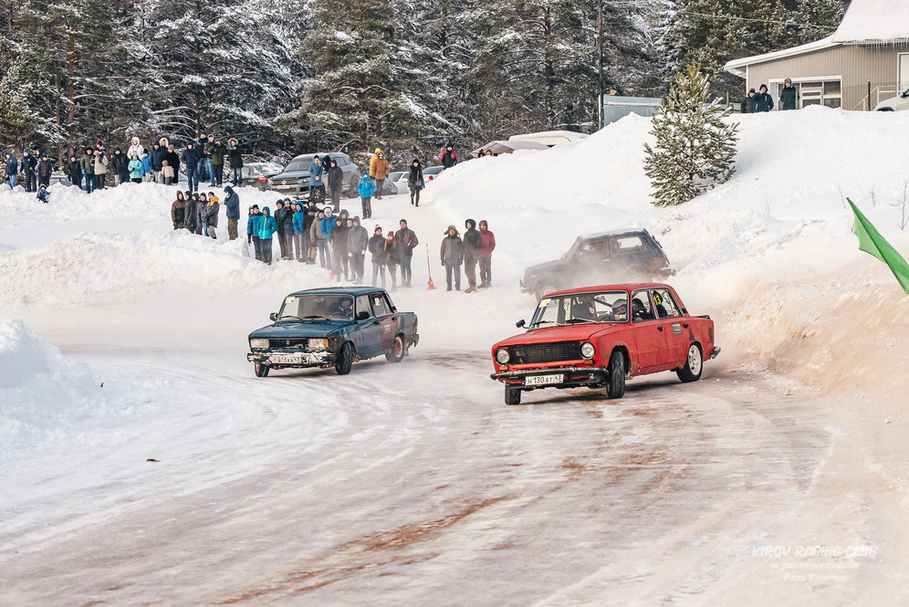 A red and a blue Soviet car compete on ice in front of group of people during the first stage of Ice Drift Kirov, Russia, 2018.