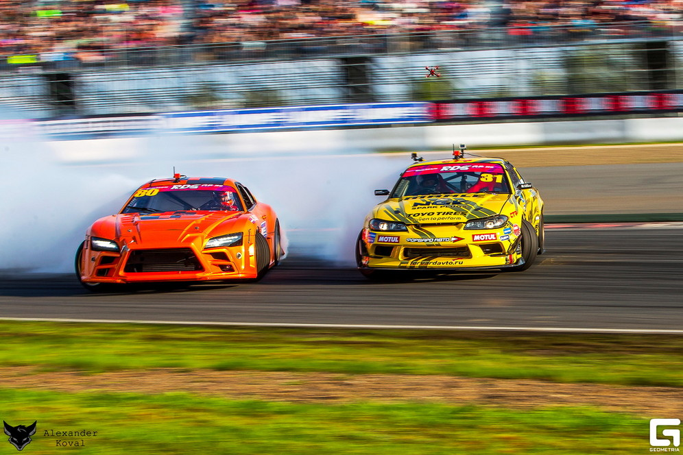An orange and a red car emit smoke as they skid side by side around a corner of the track during Russian Drift Series competition in the  2018 drift racing championship