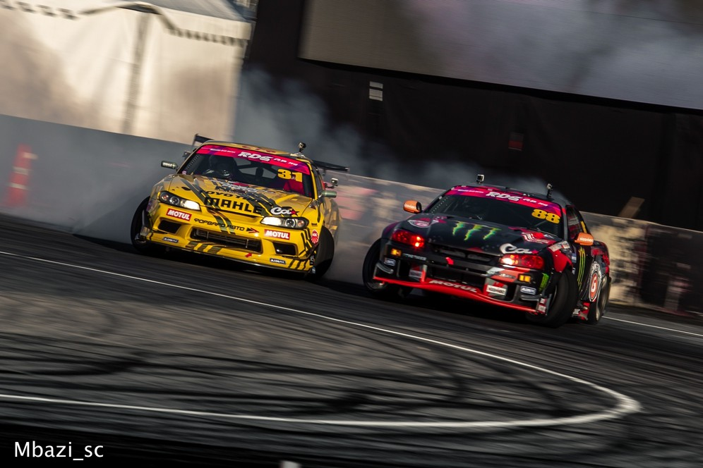 A yellow car and a black car skid round a bend in a stage of the Russian Drift Series car racing championship