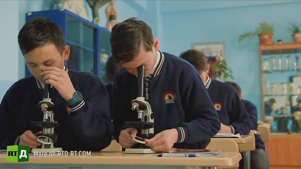 In the classroom of a Turkish school in Kyrgyzstan, two boys look through a microscope during science class. Still taken from RTD's documentary series on Fethullah Gulen, The Gulen Mystery, Episode 1: Gulen's Schools.