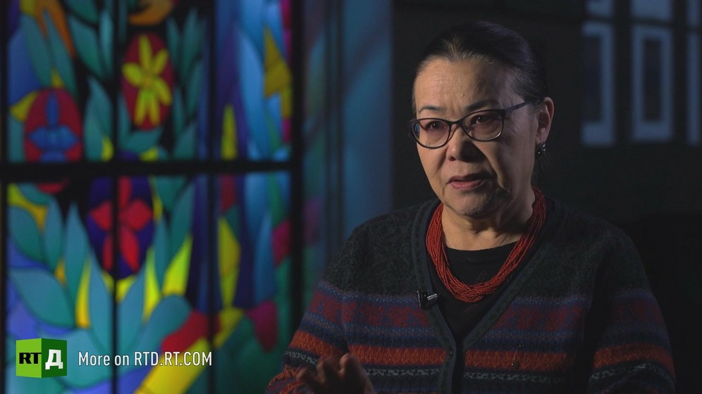 Headshot of former Kyrgyzstan education minister Ishenkul Boldzhurova sitting in front of a stained-glass window. Still taken from RTD's documentary series on Fethullah Gulen, The Gulen Mystery, Episode 1: Gulen's Schools.