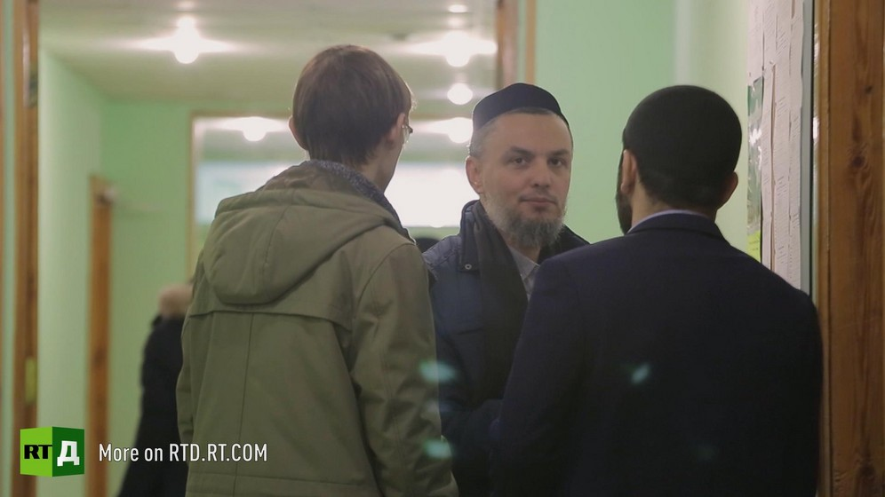 Said Damir Shagaviev wearing a traditional skullcap and a small beard is looking at the camera while talking to two men with their backs to the camera in a corridor in Kazan, Russia. Still taken from RTD's documentary series on Fethullah Gulen, The Gulen Mystery, Episode 2: Gulen's Hizmet Movement.