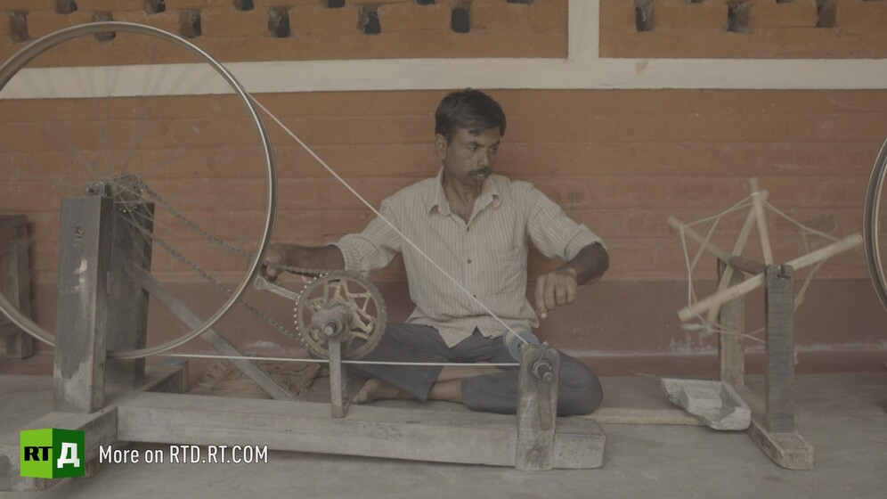 Indian man using a handspinning wheel. Still taken from RTD documentary Gandhi's Footsteps.