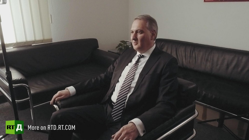 In Germany, entrepreneur Teyfik Ozcan wearing a suit and tie is sitting in a black leather armchair, surrounded by two sofas. Still taken from RTD's documentary series on Fethullah Gulen, The Gulen Mystery, Episode 3: Gulen's Businessmen.