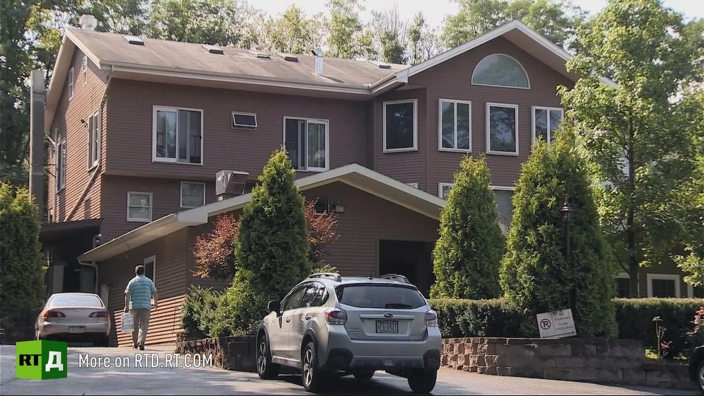 View of the house where Fethullah Gulen lives in Pensylvania, surrounded by trees, with two cars in the drive and one man in the background. Still taken from RTD's documentary series on Fethullah Gulen, The Gulen Mystery, Episode 4: Gulen's Turkish Charter Schools.