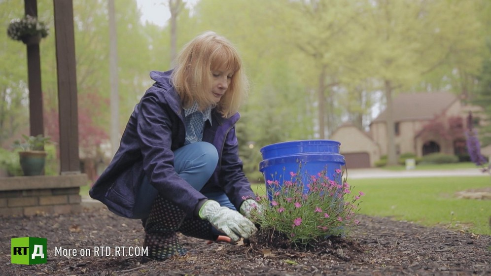 Full shot of Mary Addi crouching to cut flowers while wearing gardening gloves. Still taken from RTD's documentary series on Fethullah Gulen, The Gulen Mystery, Episode 4: Gulen's Turkish Charter Schools.