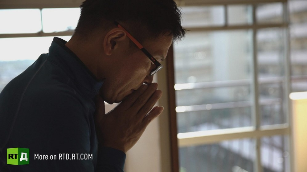 Japan's 'lonely death', or 'Kodokushi', cleaner says a prayer before starting work in an apartment. A screenshot from Dying Alone documentary