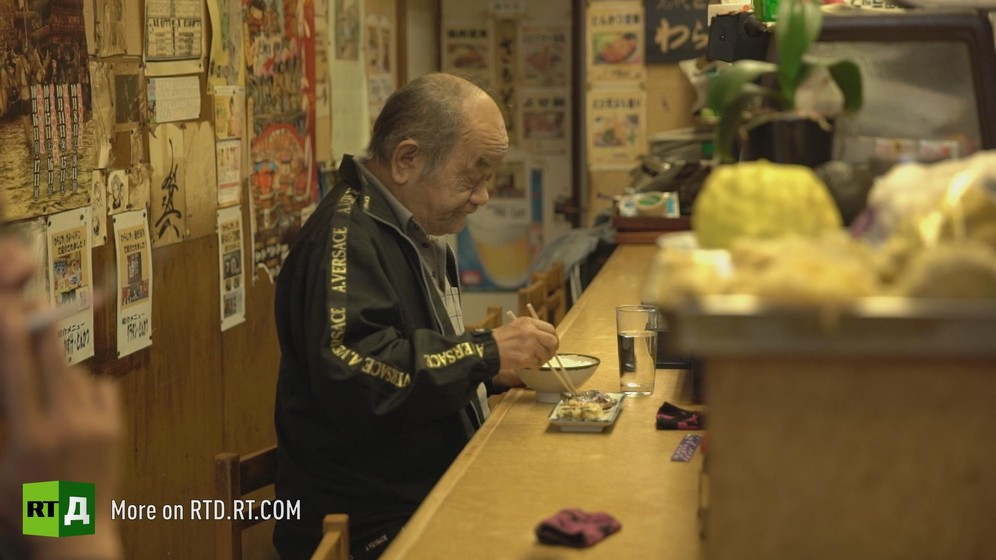 A lonely Japanese old man eating in a restaurant. A screenshot from Dying Alone documentary