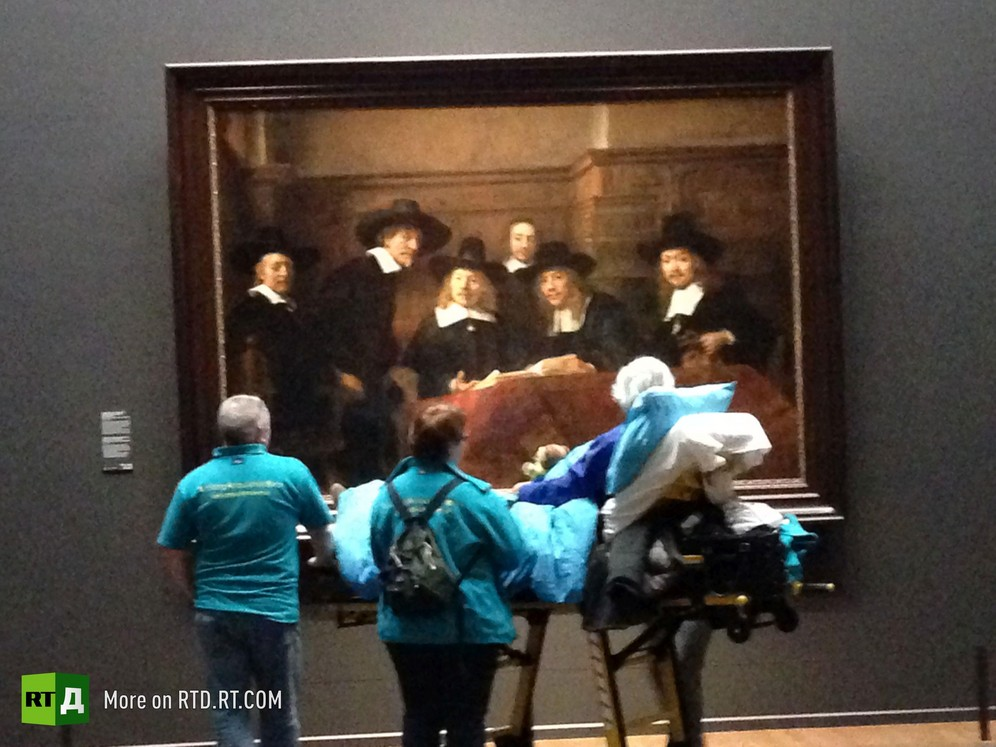 A senior male cancer patient lying on an ambulance stretcher is looking at an Old Master painting, surrounded by volunteers from the Ambulance Wish Foundation during a visit to the Rijksmuseum in Amsterdam, the Netherlands. Still from RTD documentary Last Wishes.