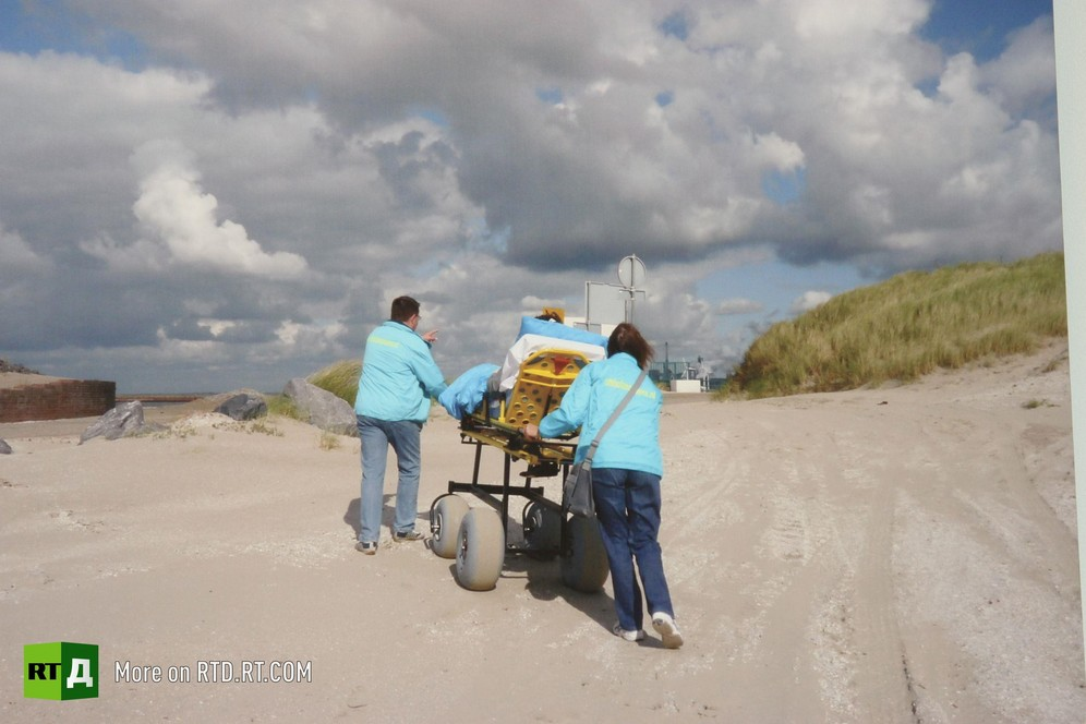 A terminally ill patient is being led along the beach in an ambulance stretcher by two volunteers from the Ambulance Wish Foundation in the Netherlands. Picture taken during filming of RTD documentary Last Wishes.