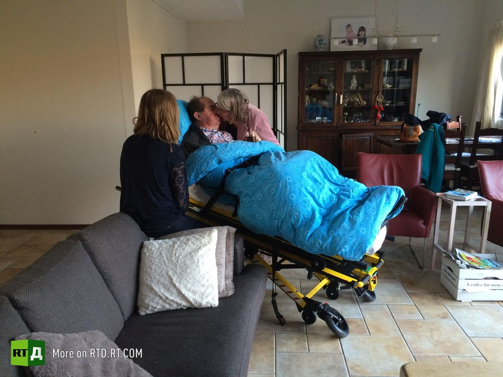 Dying patient on an ambulance stretcher, kissing his wife, with adult daughter watching, during a visit to his home made possible by the Ambulance Wish Foundation, in the Netherlands. Picture taken during filming of RTD documentary Last Wishes.