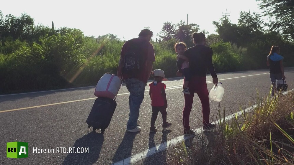 A Central American migrant family walking towards Mexico border