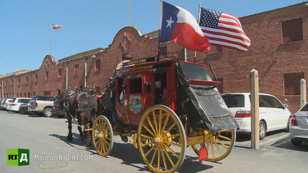A red horsedrawn stagecoach with Texas and United States flags drives through a sunny street in Texas with low-rise red brick buildings in the background. Still taken from RTD documentary The REpublic of Texas.