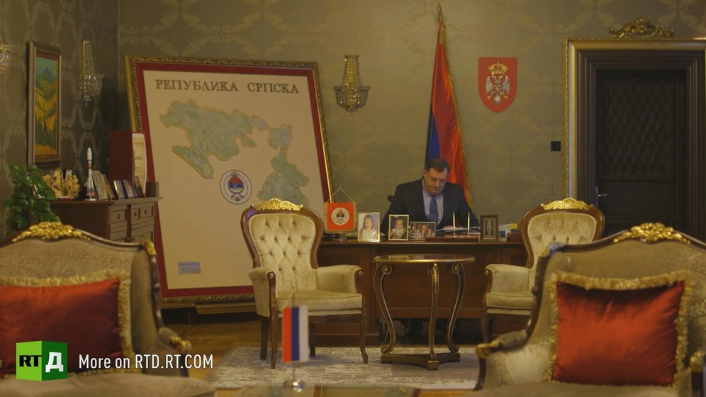 Former Republika Srpska President Miloslav Dodic, currently chairman of the Presidency of Bosnia-Herzegovina, sits at his desk in front of a flag and a large map of Republika Srpska, with velvet upholstered armchairs in the foreground. Still taken from RTD documentary Republika Srpska.