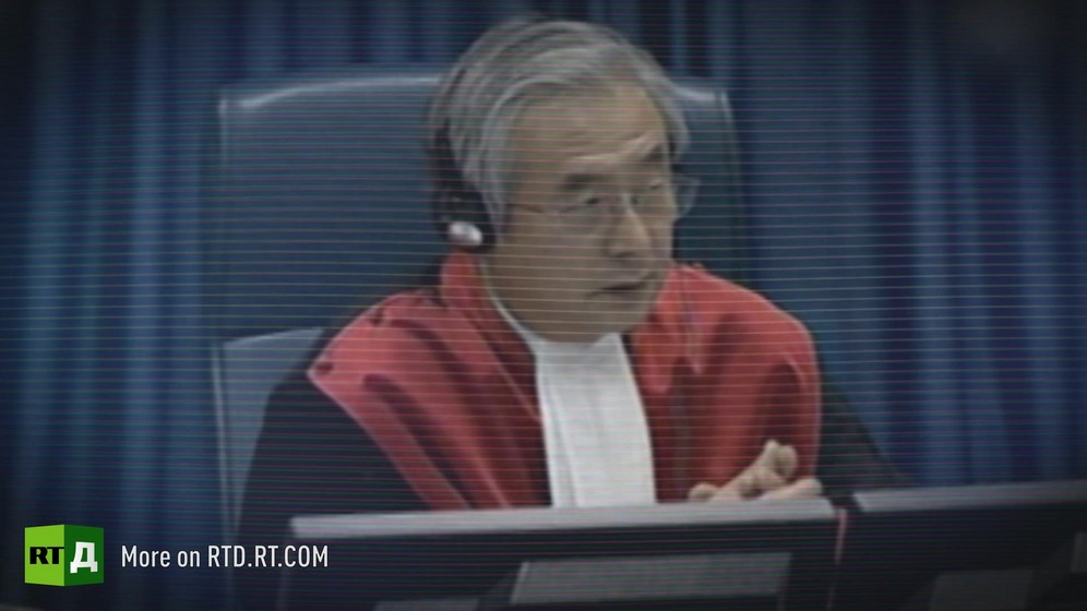 Male judge sitting in a red robe wearing headphones at the International Criminal Tribunal for the Former Yougoslavia. / Archive footage from Republika Srpska Radio and Television.