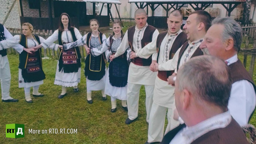 Group of young women and men from Republika Srpska in traditional costume holding hands during a dance. Still taken from RTD documentary Republika Srpska.