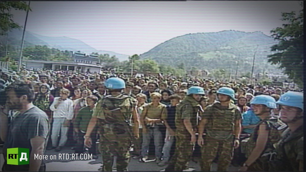 UN Peacekeeping troups in front of a large crowd, with hill in the background. Archive footage provided by Republika Srpska Radio and Television.