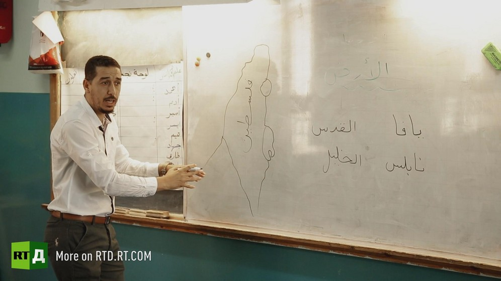 Male Palestinian schoolteacher in front of a map of the territory of greater Palestine on a white board. Still taken from RTD documentary Palestine in Seeking Recognition series.