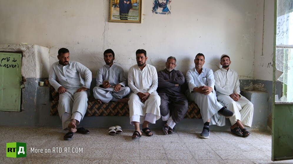 In Wadi Al-Salam cemetery in Najaf, Iraq, a group of gravediggers sit in a grave digger's office. Still taken while filming the RTD documentary Sons of the Graveyard.