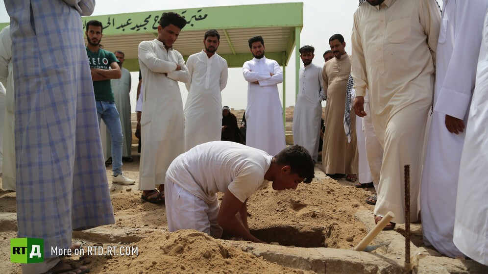In Wadi Al-Salam cemetery in Najaf, Iraq, surrounded by onlookers, a young gravedigger gets to work. Still taken while filming the RTD documentary Sons of the Graveyard.