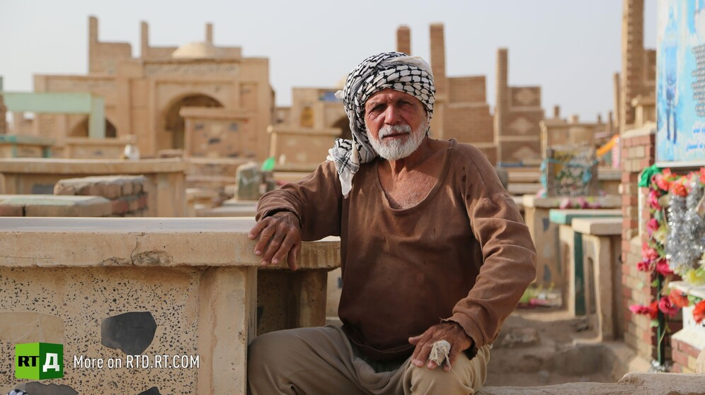 In Wadi Al-Salam cemetery in Najaf, Iraq, a gravedigger sits next to a grave. Still taken while filming the RTD documentary Sons of the Graveyard.