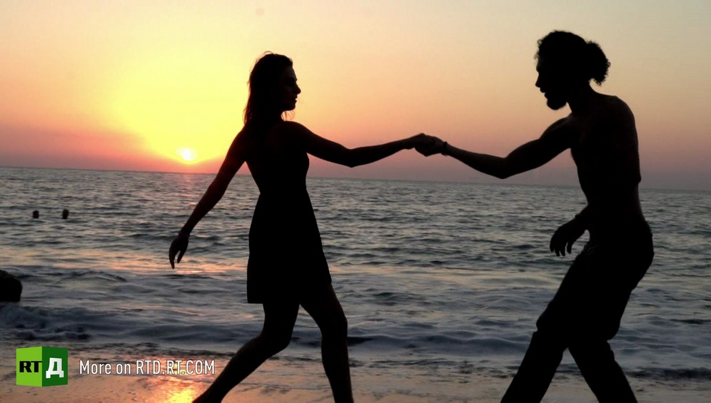 Woman and man dancing tango on the beach at sunset in Latakia, Syria. Still from Syrian Tango