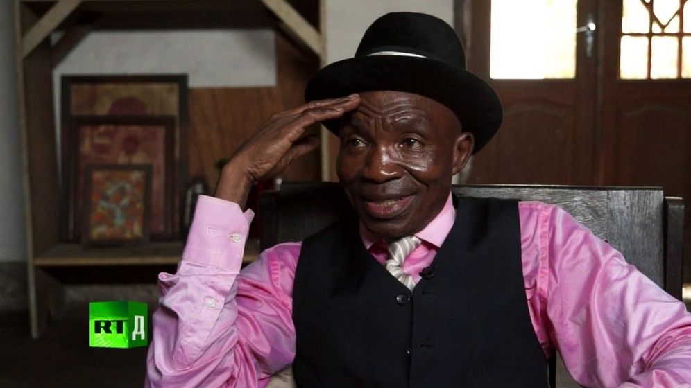 Severin Mouyengo, known as 'Le Salopard de la Sape', wearing a bowler hat, pink shirt and waistcoat. Screenshot taken from RTD documentary Congo Dandies.