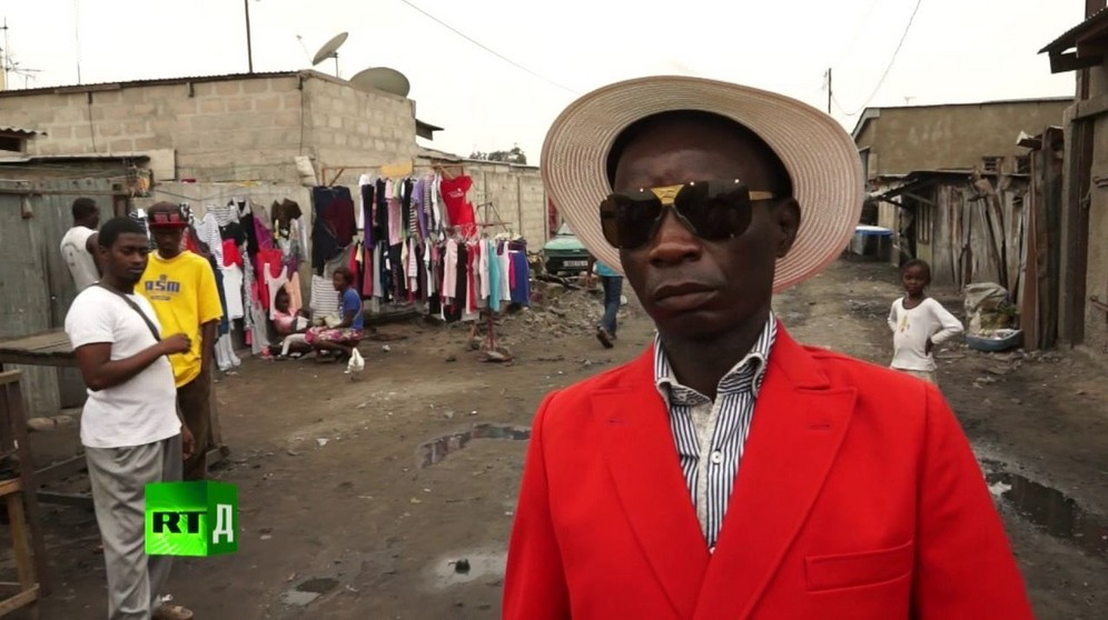 Maxime Dutoit, a famous Congo Sapeur, wearing a red jacket and straw hat on streets of Brazzaville. Screenshot taken from RTD documentary Congo Dandies.