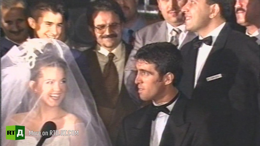 Footballer Hakan Sukur wearing a black bow tie and a tuxedo sitting next to his bride surrounded by men in suits at his wedding in Istanbul, Turkey. Still taken from RTD's documentary series on Fethullah Gulen, The Gulen Mystery, Episode 5: Turkey's Coup.