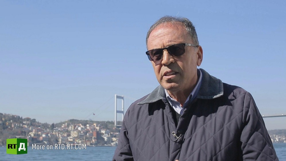 General Ahmet Yavuz wearing sunglasses is standing in front of the Bosphorus in Istanbul, Turkey, on a sunny day with bright blue skies. Still taken from RTD's documentary series on Fethullah Gulen, The Gulen Mystery, Episode 5: Turkey's Coup.