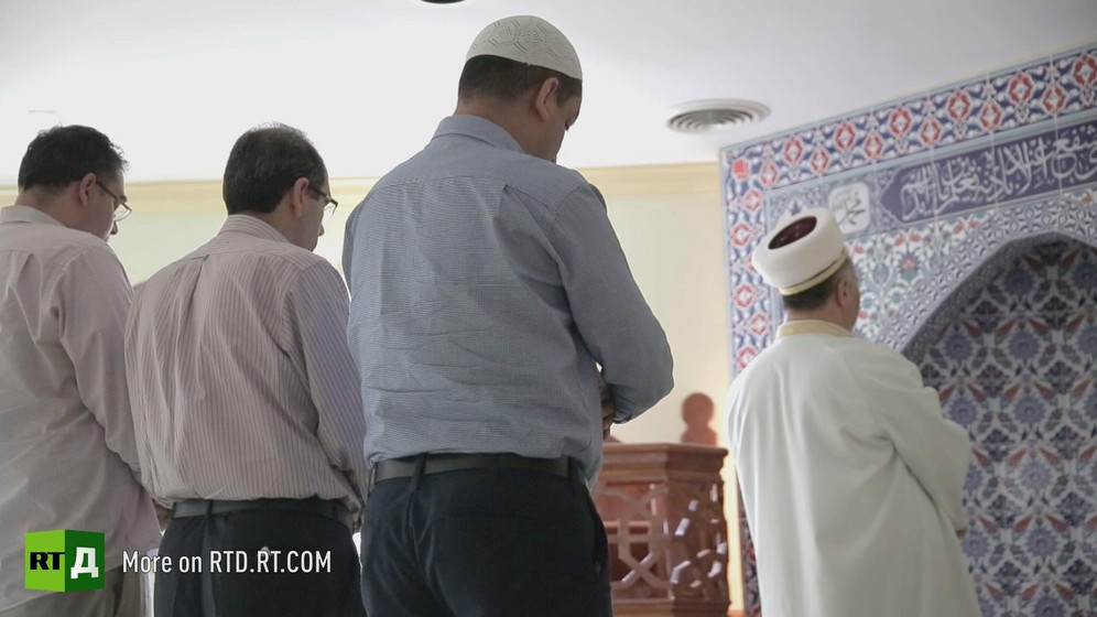 Backs of three men, one wearing a skullcap, standing behind an imam wearing a hat, also from the back, as they pray in a prayer room. Still taken from RTD's documentary series on Fethullah Gulen, The Gulen Mystery, Episode 5: Turkey's Coup.