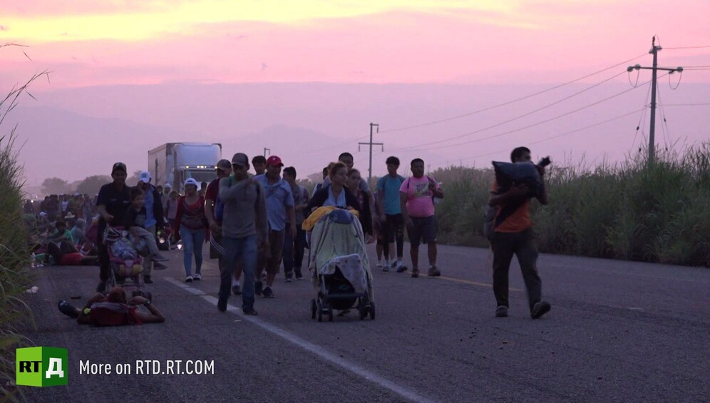 Families in the migrant caravan walking along a road at sunset. Still taken from RTD documentary