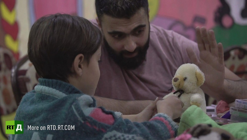 Little boy playing with teddy bear, guided by child psychologist in Aleppo Province, Syria. He was traumatised after being forced to watch beheadings by rebel fighters from Jaish Al Islam. Still taken from RTD documentary about child fighters Where Childhood Died.