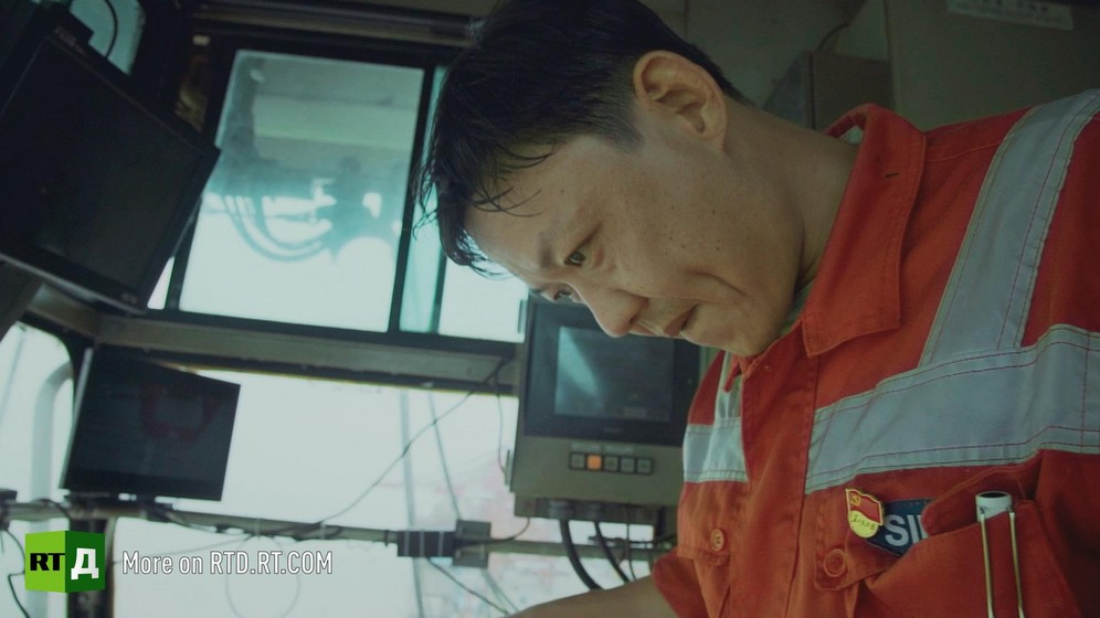 Yangshan container port, China, acrane operator looks down from cabin while unloading a container ship. Still taken from RTD documentary Yangshan City Port in the 'This is China' series.